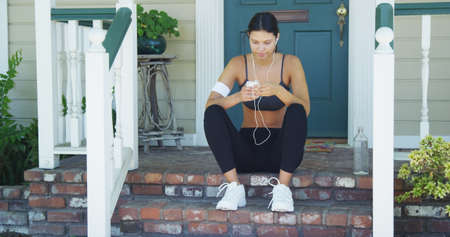 Hispanic woman starting playlist before going out for a run photo