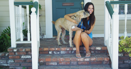 Junge Frau sitzt auf Veranda mit ihrem Hund Lizenzfreie Bilder