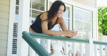fench: Mixed race woman leaning on rail texting