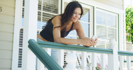 fench: Hispanic woman leaning on rail texting Stock Photo