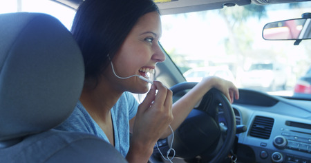 Hispanic woman talking in the car with earphones