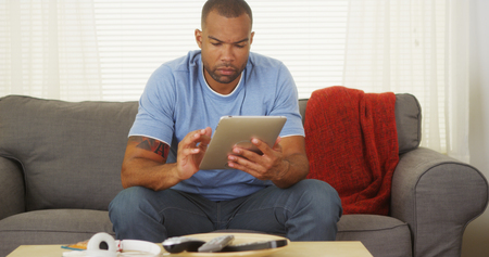 Black man sitting on couch using tablet photo