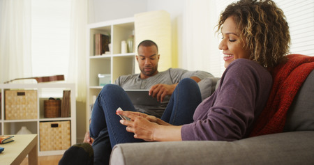 couple on couch: Black couple using electronic devices on sofa