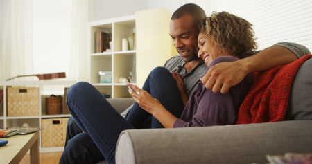 couple on couch: African American couple using devices on couch