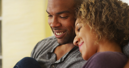 couple relaxing: Black couple sitting on couch smiling