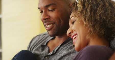 couple on couch: Black couple sitting on couch smiling