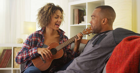 serenading: Black girlfriend serenading her boyfriend with ukulele Stock Photo