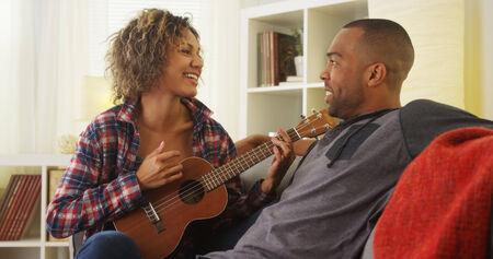 serenading: Cute black girlfriend serenading her boyfriend with ukulele