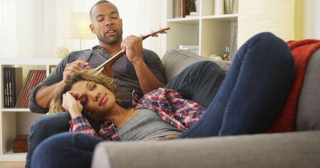 serenading: African boyfriend serenading his girlfriend with ukulele