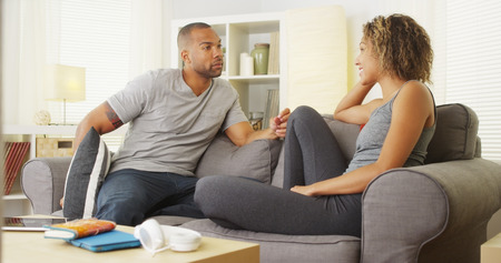 woman serious: Black couple having a conversation in their living room