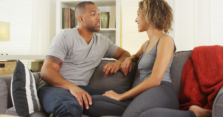 African couple talking together on couch Stock Photo