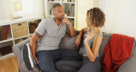 Black couple talking together on couch