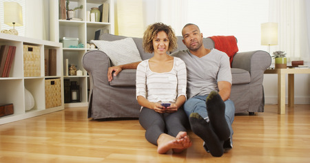 Cute black couple sitting on floor in living room photo