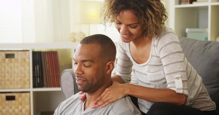Black girlfriend giving boyfriend massage Stock Photo