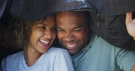 sotto la pioggia: Coppia nera in piedi sotto il cappotto cercando di non bagnarsi