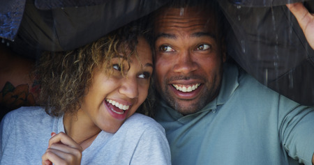 Black couple standing under coat trying not to get wet photo