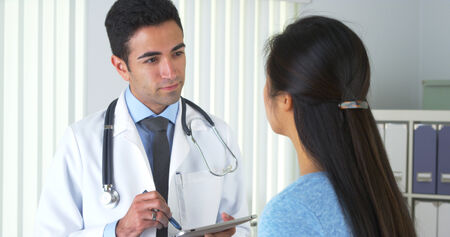 Chinese patient talking to hispanic doctor photo