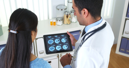 healthcare office: Mexican doctor explaining brain scans to patient