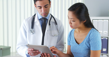 tablet: Hispanic doctor talking with patient with test results on tablet