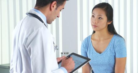 Hispanic doctor asking Asian patient questions Standard-Bild