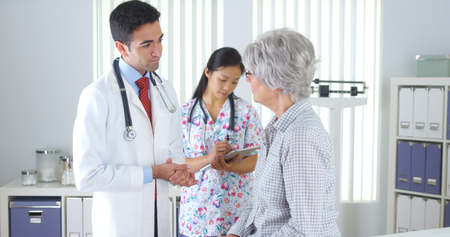 Chinese nurse weighing elderly patient photo