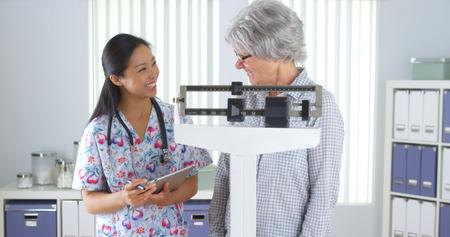 Chinese nurse weighing elderly patient Standard-Bild
