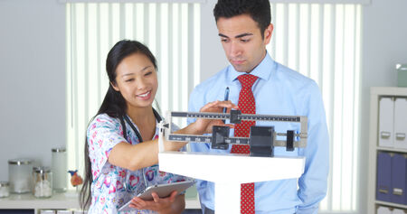 weight machine: Chinese nurse weighing Mexican patient