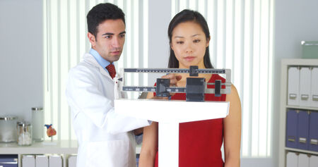Mexican doctor weighing Chinese patient photo