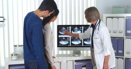tells: Senior doctor tells interracial couple about pregnancy Stock Photo