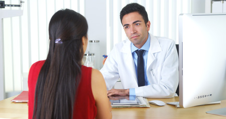 Mexican doctor reviewing xrays with patient at desk