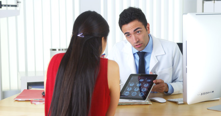 Hispanic doctor reviewing brain xrays with patient at\ desk