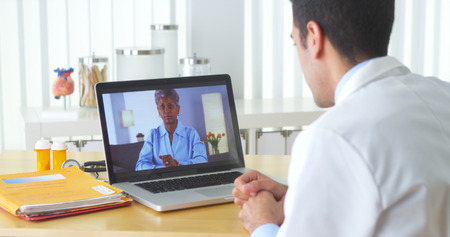 consultation woman: African patient video chatting with elderly patient