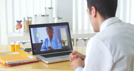 consulta médica: Vídeo paciente africano conversando con el paciente de edad avanzada