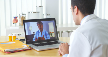 man using computer: Mexican doctor video chatting with mature patient
