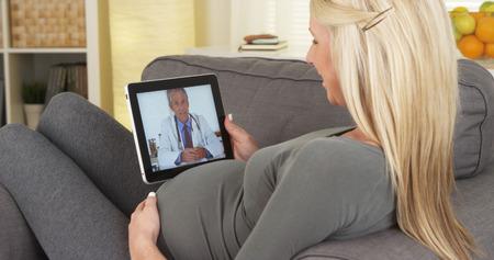 美しい妊婦のタブレット上の医者と楽しくチャット