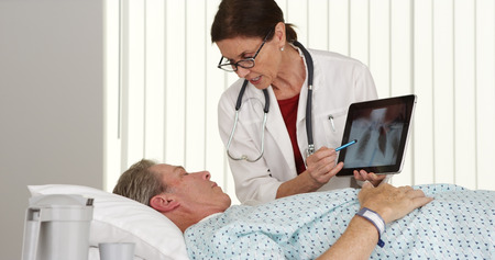 Senior woman doctor talking to elderly patient lying in bed photo