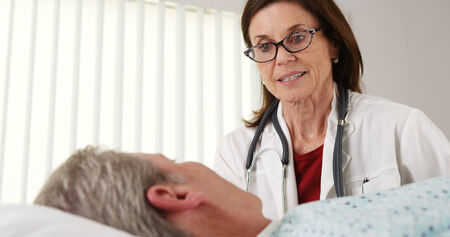 Professional doctor talking to elderly patient in bed photo