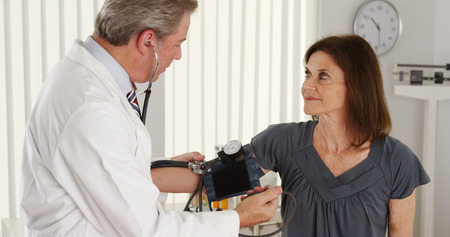 Senior doctor checking patients blood pressure photo