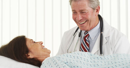 Senior doctor talking and making patient smile photo