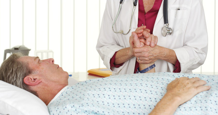 Doctor holding patients hand and comforting him photo