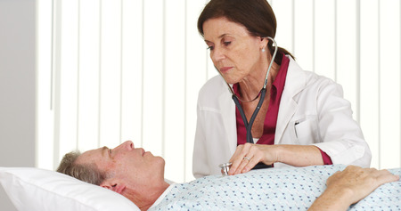 Senior doctor listening to mature patient's heart 스톡 콘텐츠