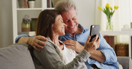 Happy senior couple using smartphone on couch