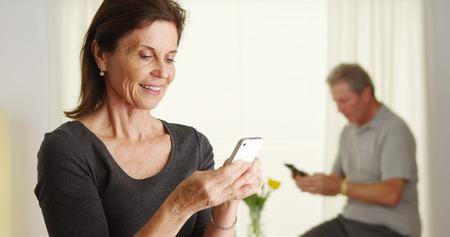 Happy senior woman using smartphone Standard-Bild