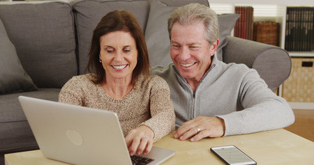 Happy senior couple using laptop on coffee table