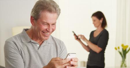 Cheerful senior man using smartphone Standard-Bild