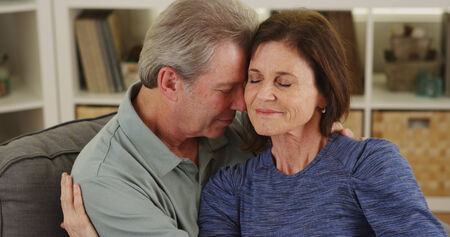 couple on couch: Loving senior couple cuddling on couch