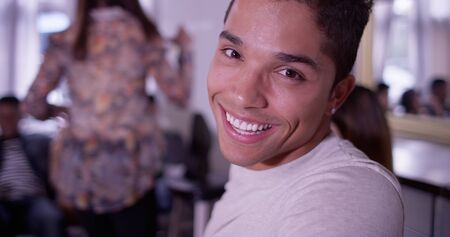 partying: Portrait of Handsome young mixed race hipster man smiling at camera with group of friends partying in background