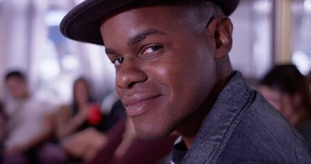 partying: Portrait of Handsome young black hipster man smiling at camera with group of friends partying in background