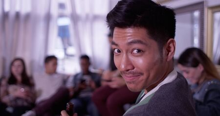 partying: Portrait of Handsome young asian hipster man smiling and laughing with group of friends partying in background Stock Photo