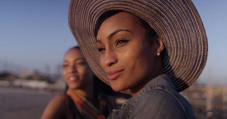 amigas conversando: Las mujeres negras mejores amigos que mira hacia fuera sobre el océano mientras está de pie en el muelle